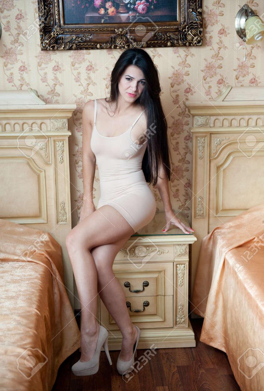 junge schöne sexy frau im weißen kurzen, engen kleid posiert anspruchsvolle  innen im vintage-hotelzimmer. sinnliche brünette lange haare weiblich