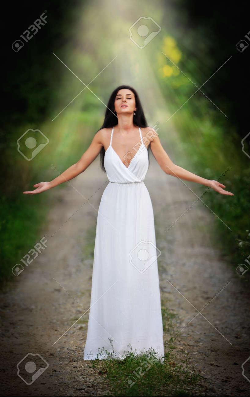 c6f8f25e5 Señora Joven Encantadora Que Llevaba Un Elegante Vestido Blanco Largo  Disfrutando De Los Rayos De Luz Celestial En Su Cara En Bosques Encantados.