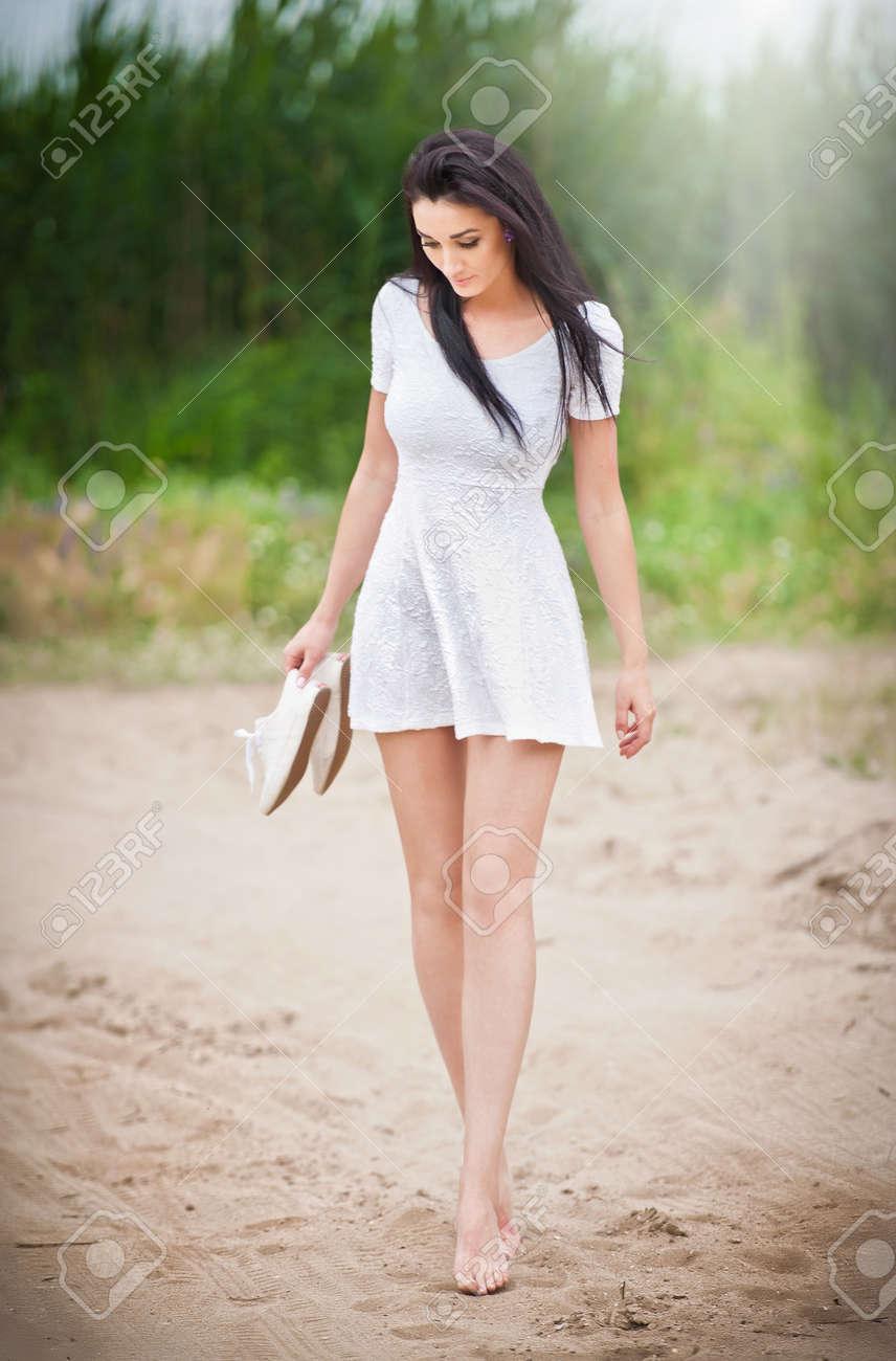 attraktive brünette mädchen mit kurzen weißen kleid spazieren barfuß auf  dem land unterwegs. junge schöne frau zu fuß mit schuhen in der hand mit  wald