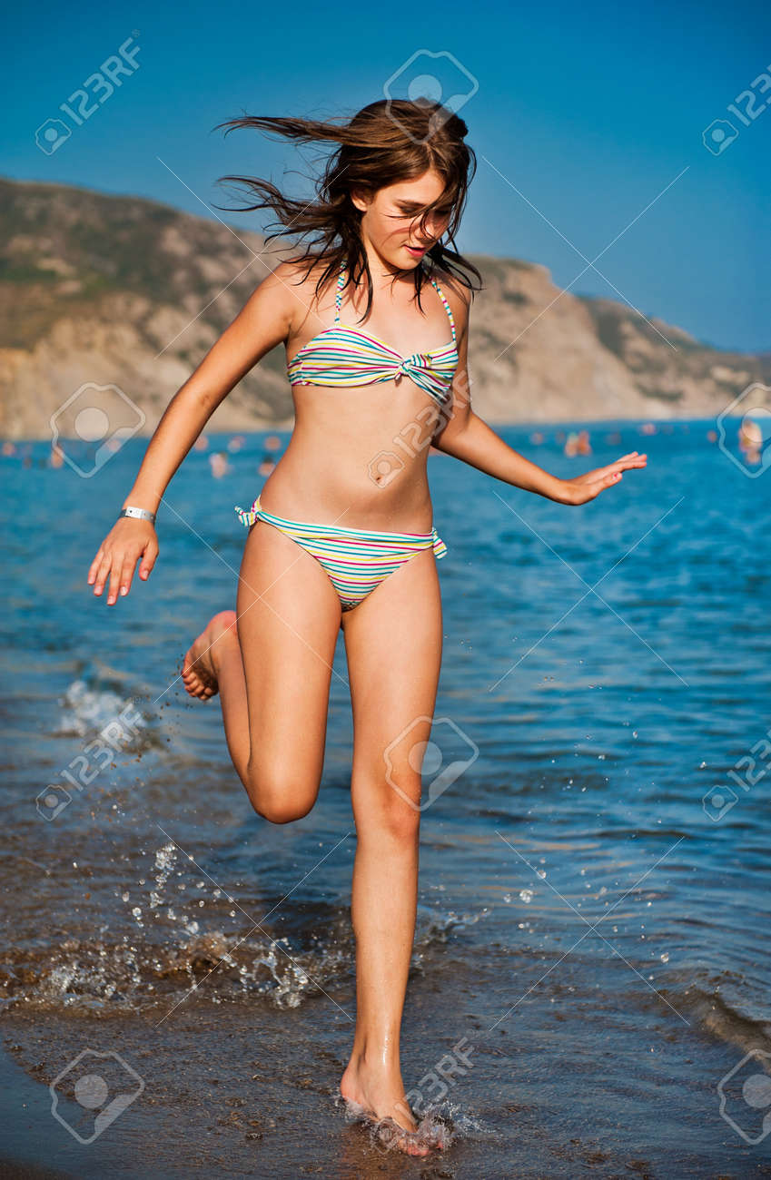 Young Teen Girl Playing With Waves At The Beach Stock Photo