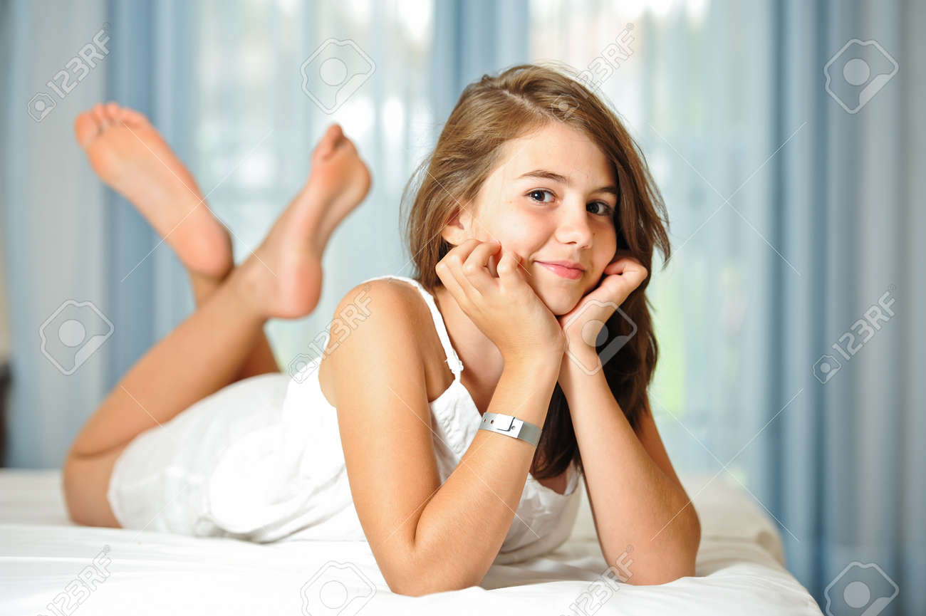 b05d4e552d Portrait of smiling beautiful teen girl at home in white dress and relaxing  on comfortable bed