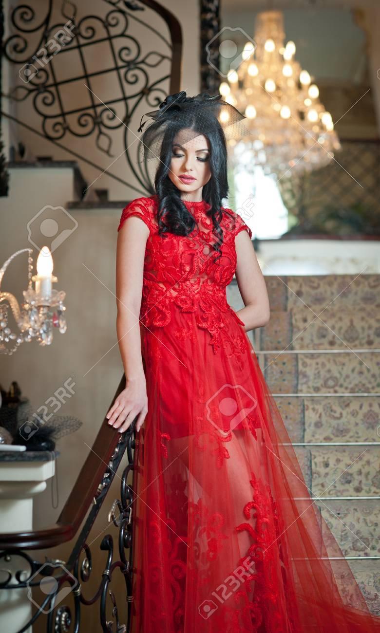 beste kwaliteit brede variëteiten grootste korting Het mooie meisje in een lange rode jurk poseren in een vintage scène. Jonge  mooie vrouw die een rode kleding in een oud hotel draagt. Sensuele ...
