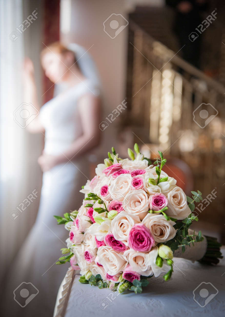 Bride In Window Frame And Wedding Bouquet In The Foreground Stock