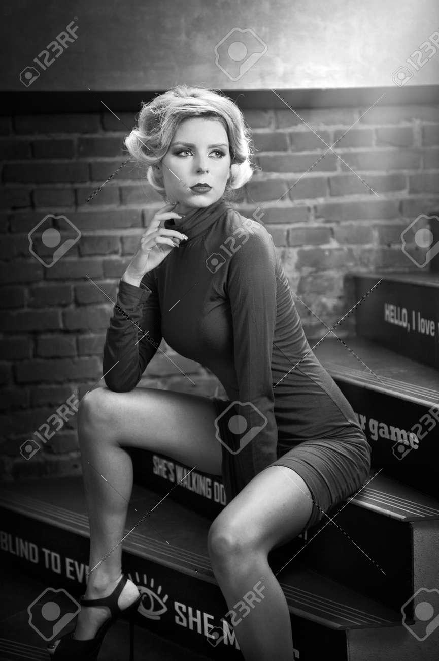 junge schöne kurze haare blonde frau in rollkragen engen kurzen kleid sitzt  auf der treppe, schwarz-weiß-foto. romantische mysteriöse dame mit