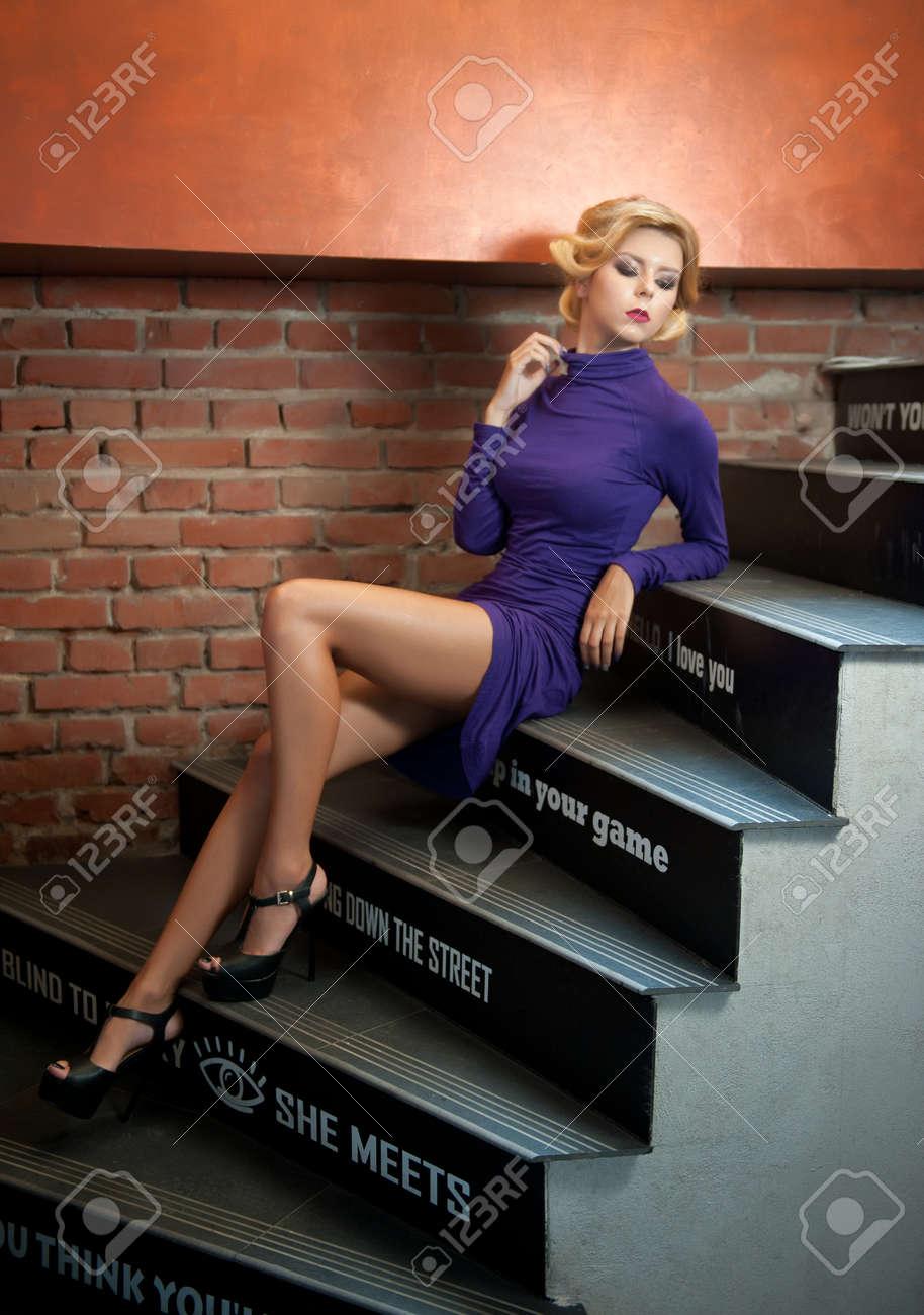 junge schöne kurze haare blonde frau in lila rolli engen kurzen kleid sitzt  auf der treppe. romantische mysteus dame mit filmstar retro-look