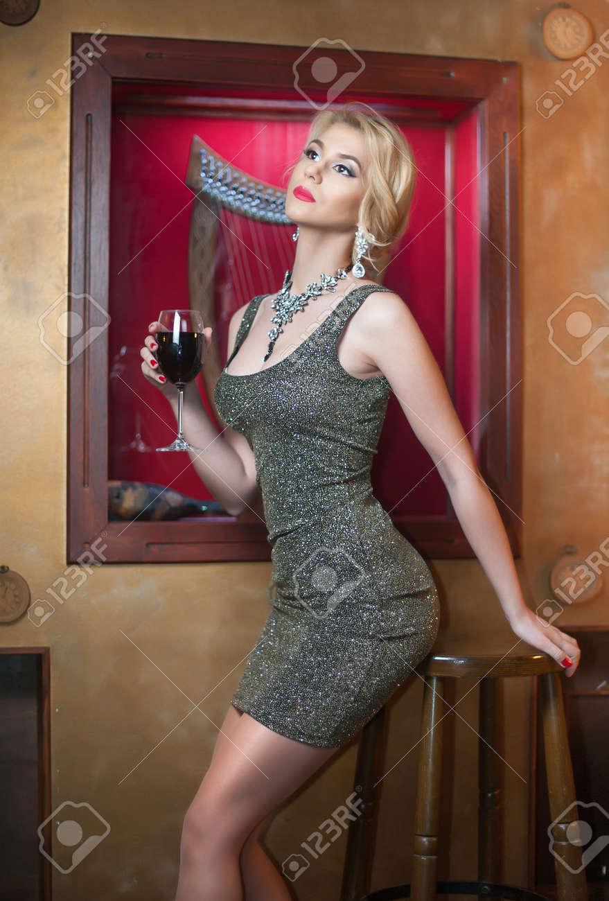 De Assis Belle Courte Verre De Posant Provocante De Vin Sur Femme Et Jolie Le Tenant Fille Courte Vêtue Sexy Un D'argent Robe D'une Façon Portrait Serrée wRgwzr