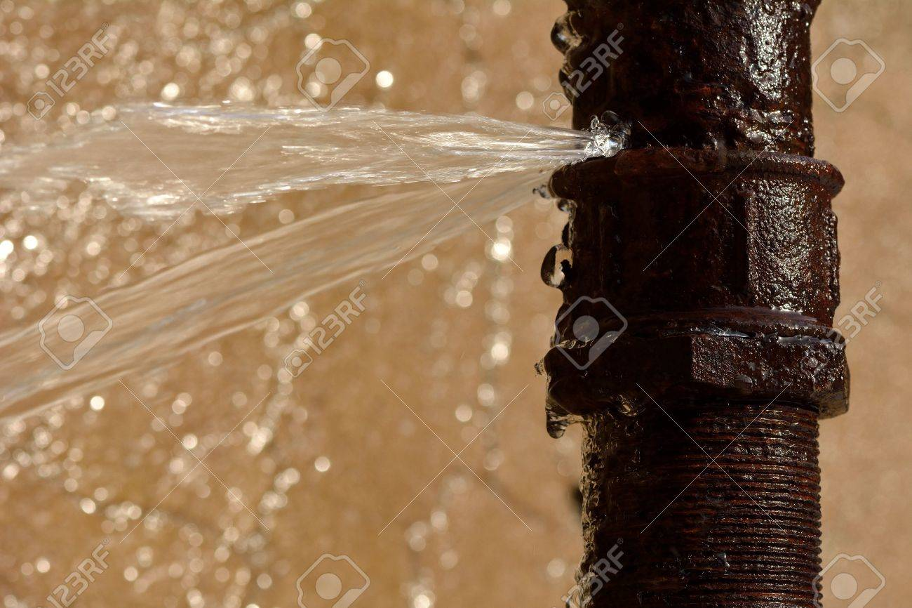 Rusty burst pipe spraying water. Old pipe leaking after freezing in winter - 63010371