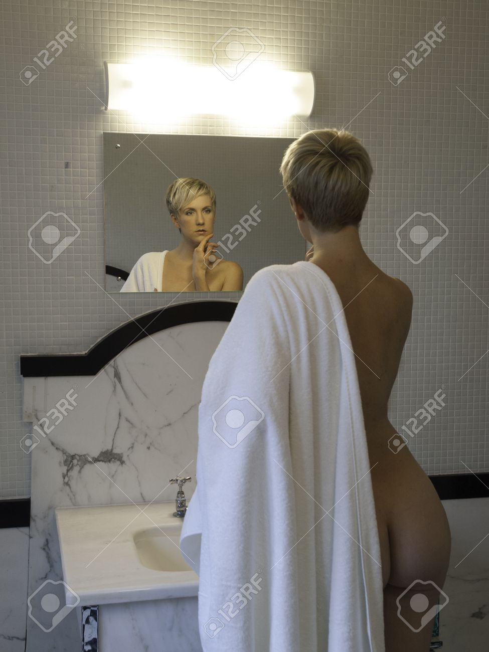 Naked woman in the bathroom looking at the mirrow Stock Photo - 18094165