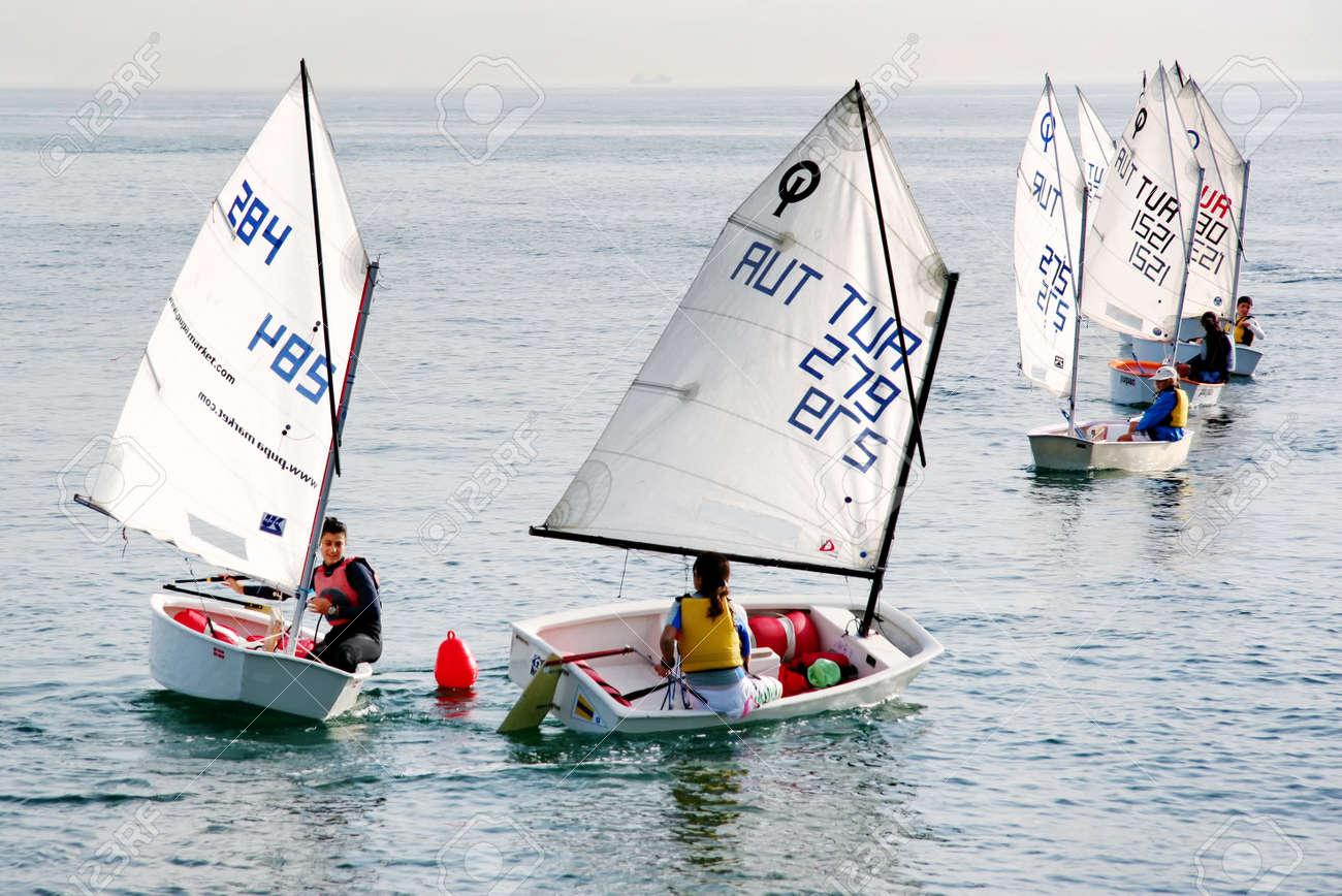 Istanbul, Turkey - November 2, 2008 : Girls train on optimist class yachts at Marmara sea. Sailors turn around red buoy - 9420072