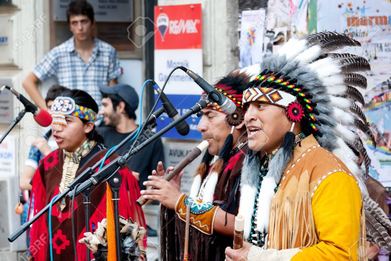 Unidentified Amerindians perform in traditional costumes during street show at Istiklal Street on July 06, 2010 in Istanbul. Beyoglu district is the major strolling street in city. Stock Photo - 9501100