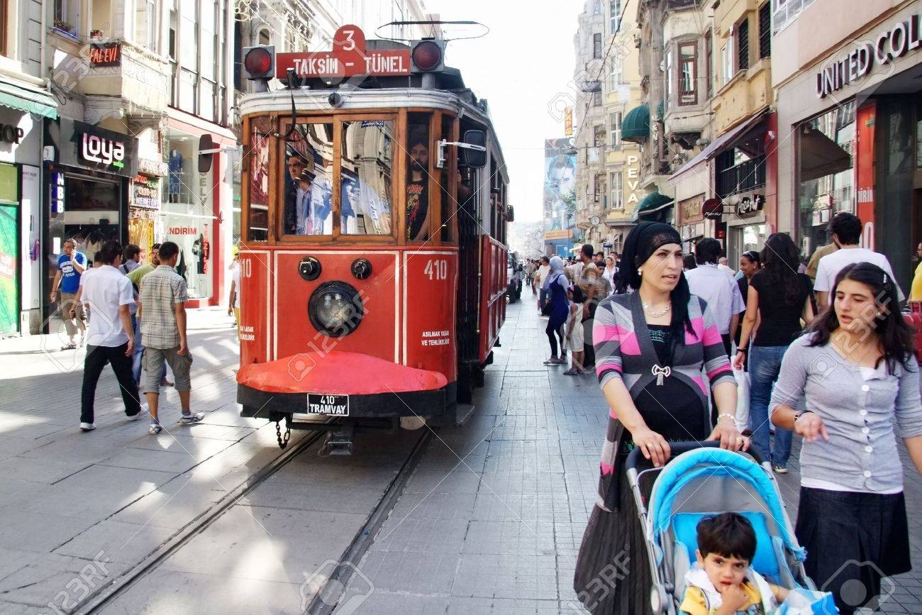 ISTANBUL - JULY 06: Unidentified mother has 4 years old child enjoy themselves at Istiklal Street on July 06, 2010 in Istanbul. Istiklal St. is busiest shopping street and famous with nostalgic trams - 9541482