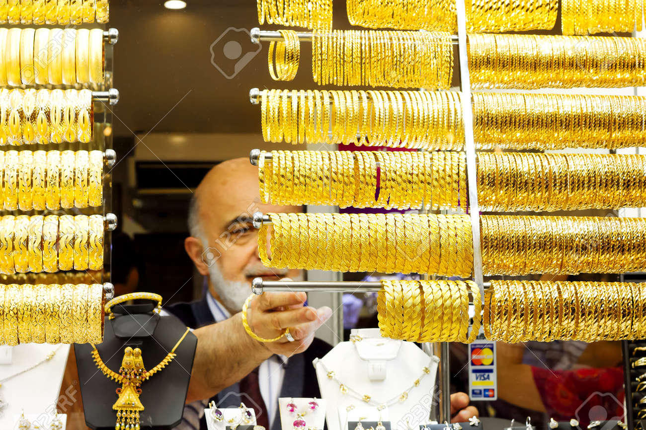 ISTANBUL - JUNE 9: Old sales man lines up bracelets on display at Grand Bazaar on June 9, 2011 in Istanbul. Turkish gold jewellery is a unique heritage which has been passed on from Romans and Ottomans - 9774393