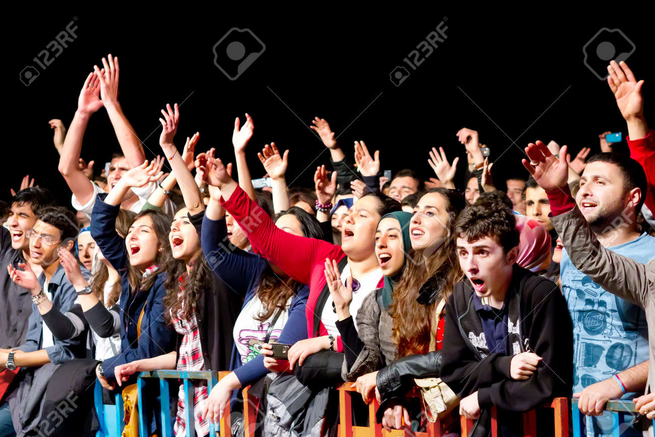 ISTANBUL - MAY 19 : Unidentified fans cheer up during pop singer Feridun Duzagac performing live for national youth festival at Maltepe open air stage on May 19, 2011 in Istanbul, Turkey. - 9890658