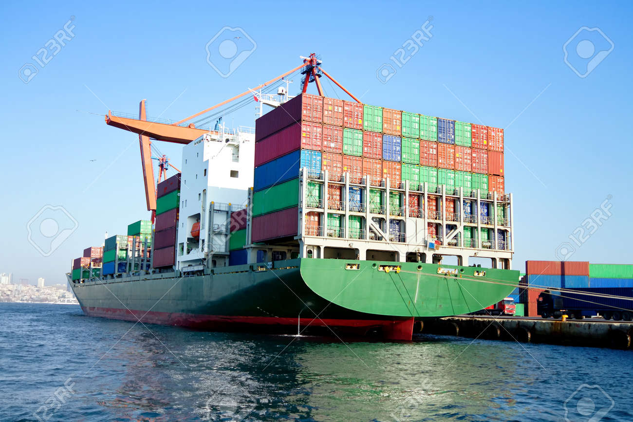 Green cargo ship in port, fully loaded with containers - 12071573