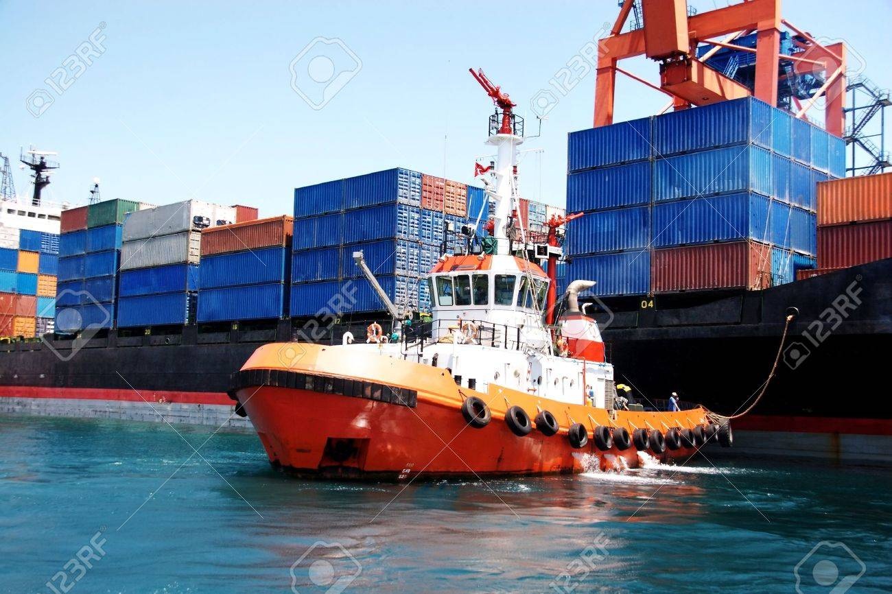 Tug boat pulling out a container ship - 12734825
