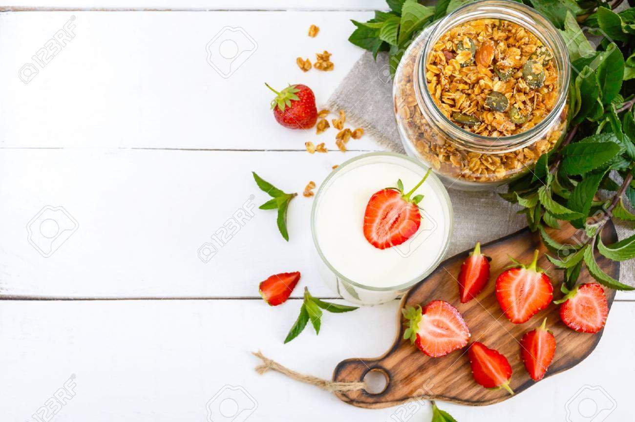 Yogurt, fresh ripe strawberry, granola - dietary dish on a white wooden table. Proper nutrition. Healthy breakfast. - 80268157