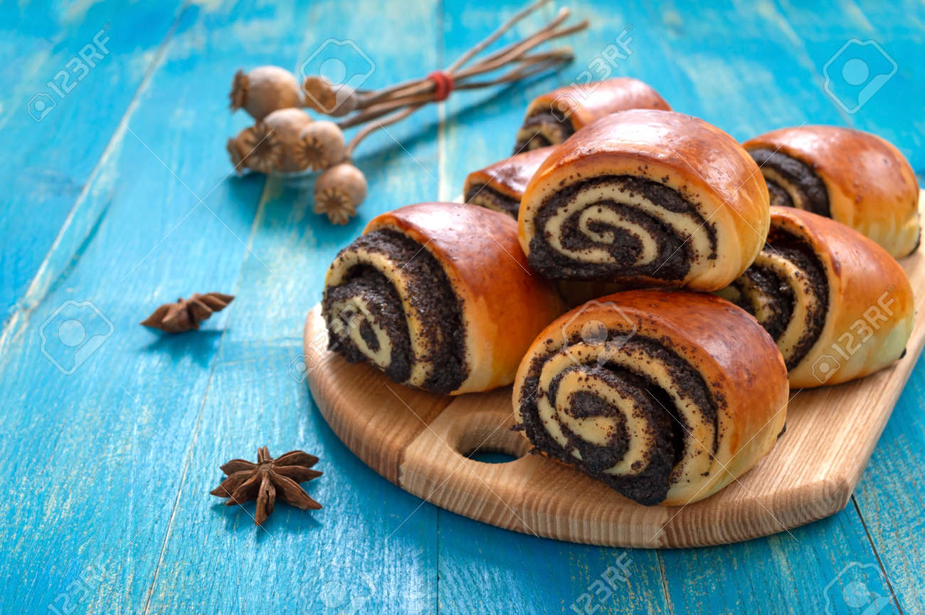 Tasty buns rolls with poppy filling on a blue wooden background. - 152261756