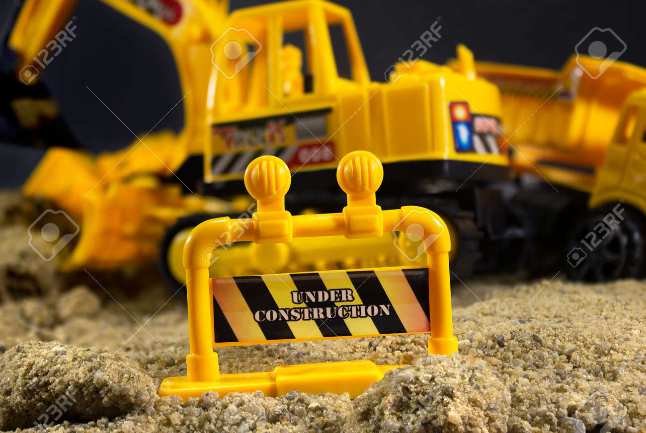 Construction Warning Sign Close Up View With Yellow Equipment On Background Stock Photo