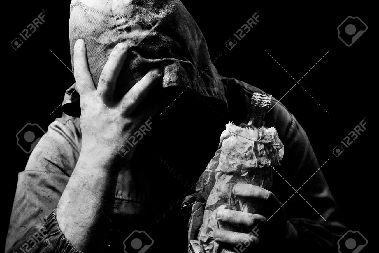 Black and white photo of emotionally depressed homeless man in hood with alcohol bottle in his