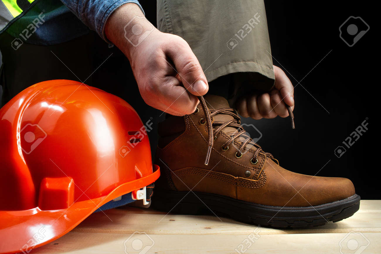 Photo of a worker lacing up leather boot on a surface with protective helmet. - 125952884