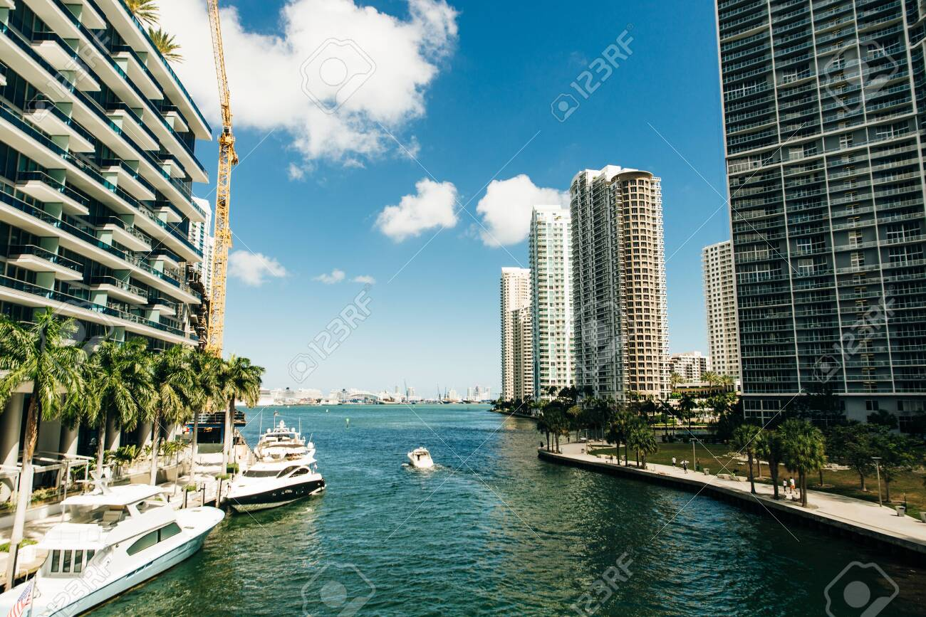 Downtown Miami along the Miami River inlet with Brickell Key in the background and yacht cruising by - 148314358