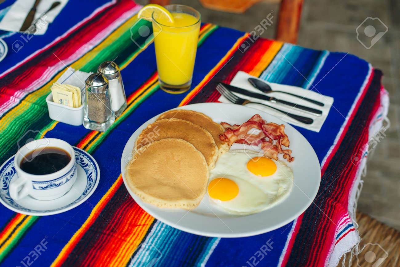 Tasty breakfast with pancakes, fried eggs and bacon on table. - 169530133