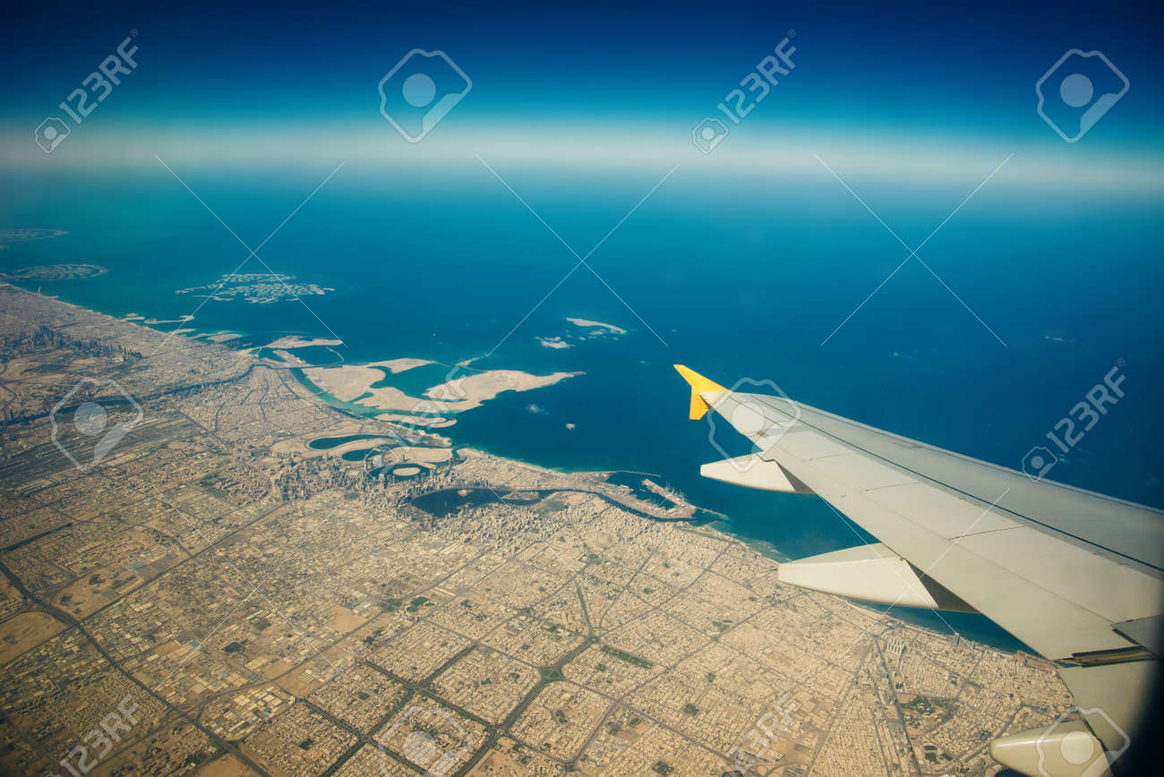 Plane window view of clouds and islands surrounded by sea and airplane wing. Traveling concept. - 169531161