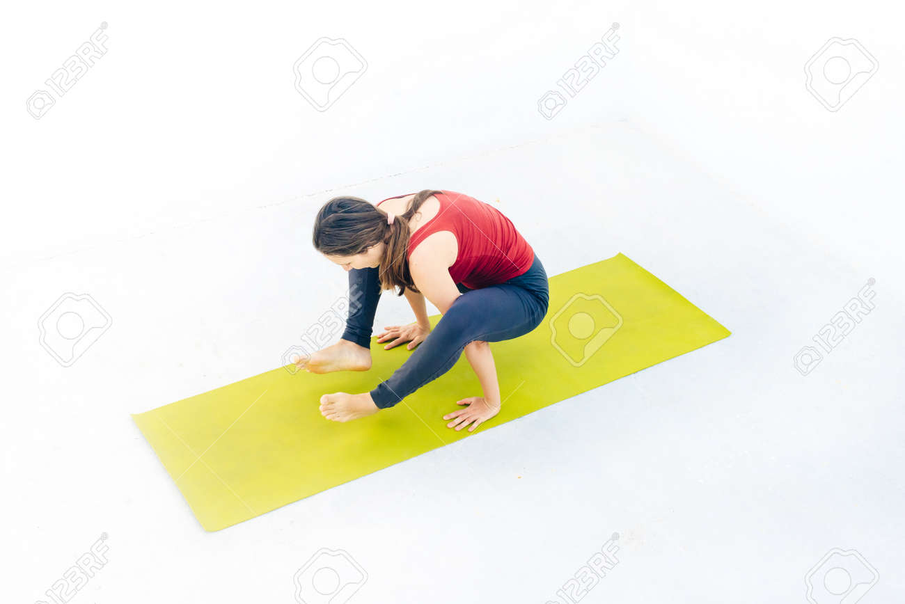 Side view portrait of beautiful young woman doing yoga or pilates exercise. - 169580045