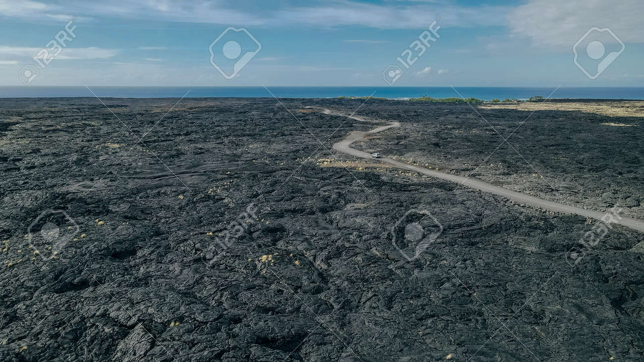 Chain of Craters Road in Hawaii Volcanoes National Park is vivid with blue ocean, waves and black sea cliffs. Cliffs were formed when Mauna Ulu exploded liquid lava. - 170120304