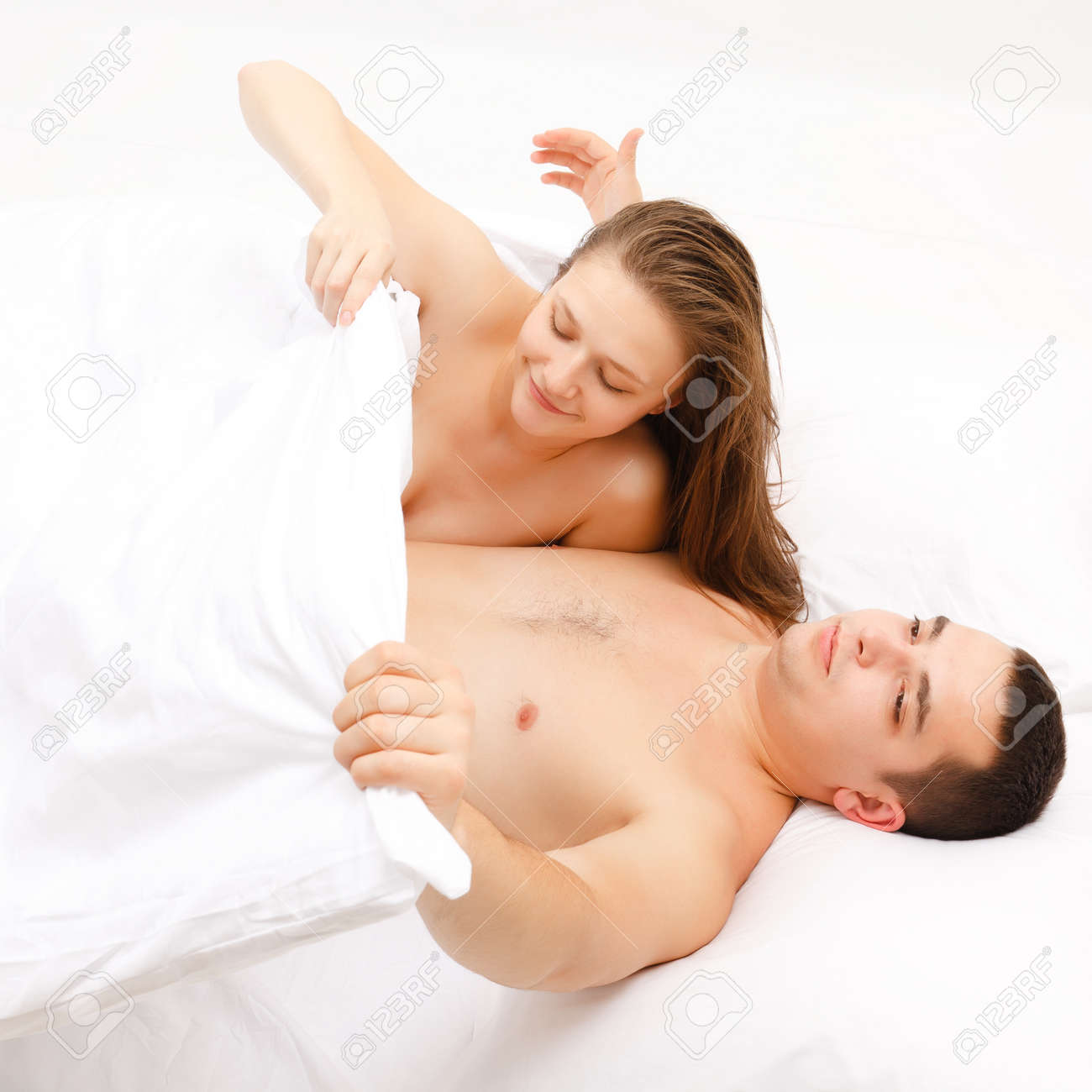 Young couple in bed, woman looking at the man's private part Stock Photo - 8922831
