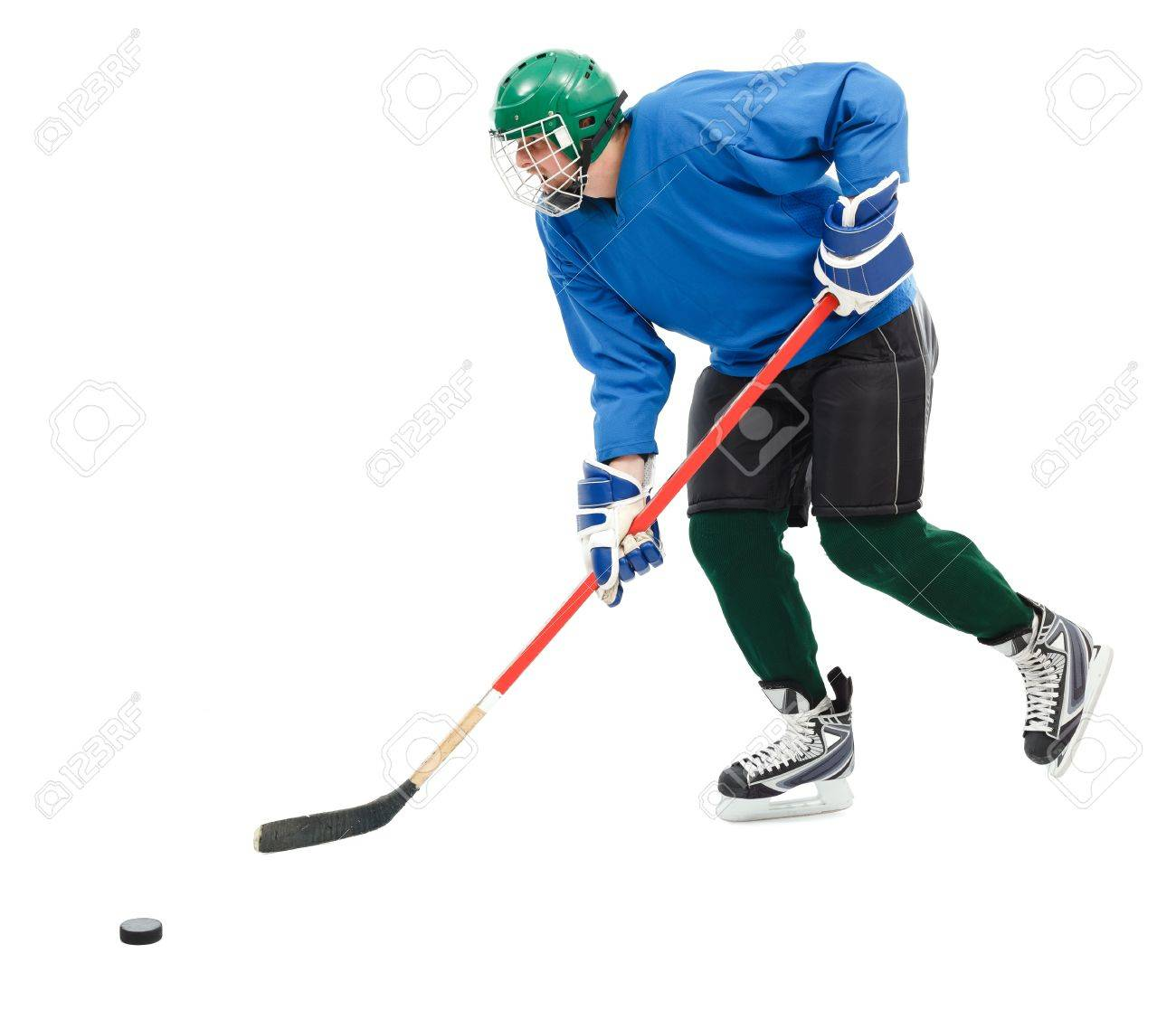 Ice hockey player in blue wear, skating fast and handling puck Stock Photo - 9198073