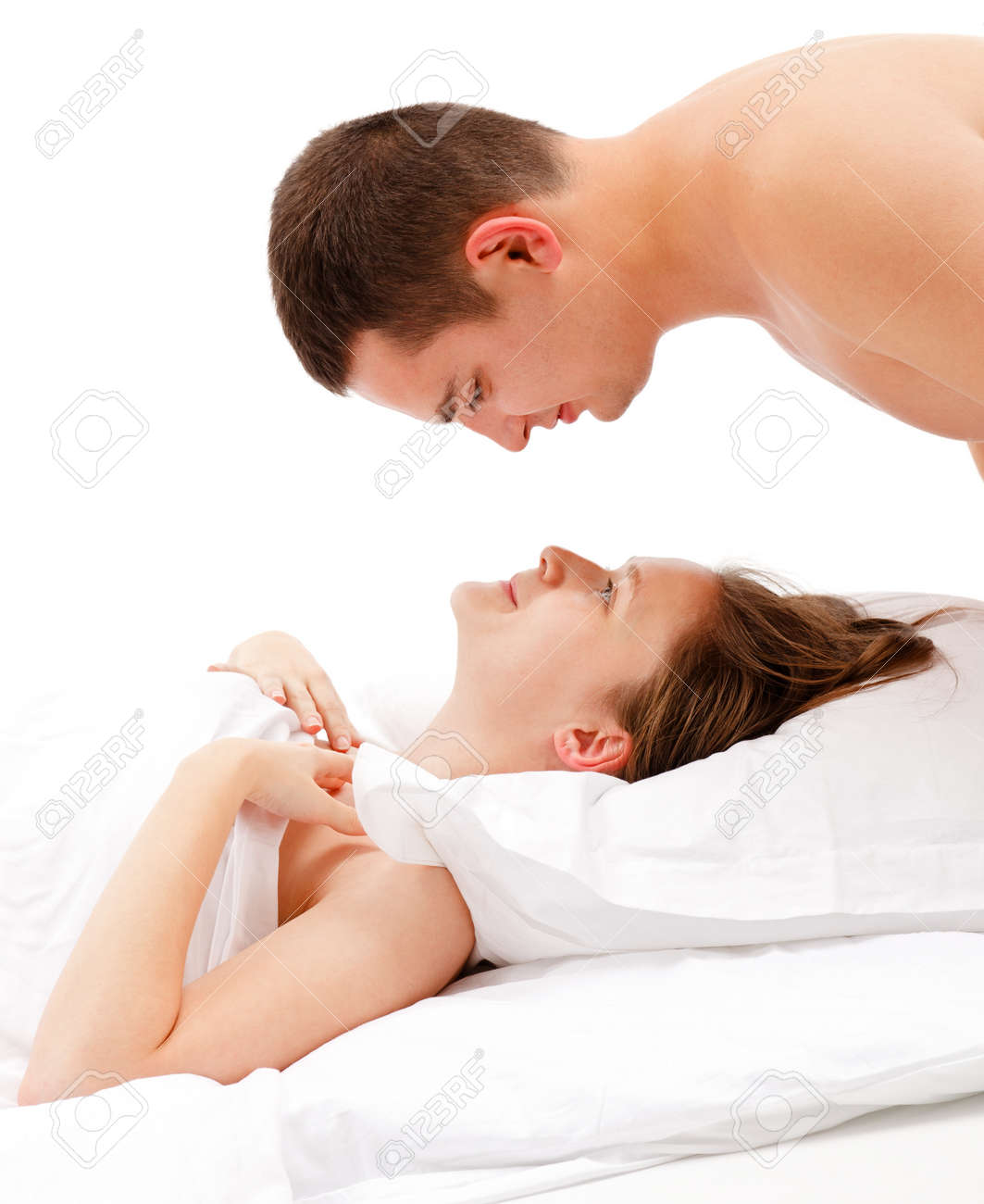 Young man looking down on young smiling woman laying in bed, covered with white quilt Stock Photo - 10658845