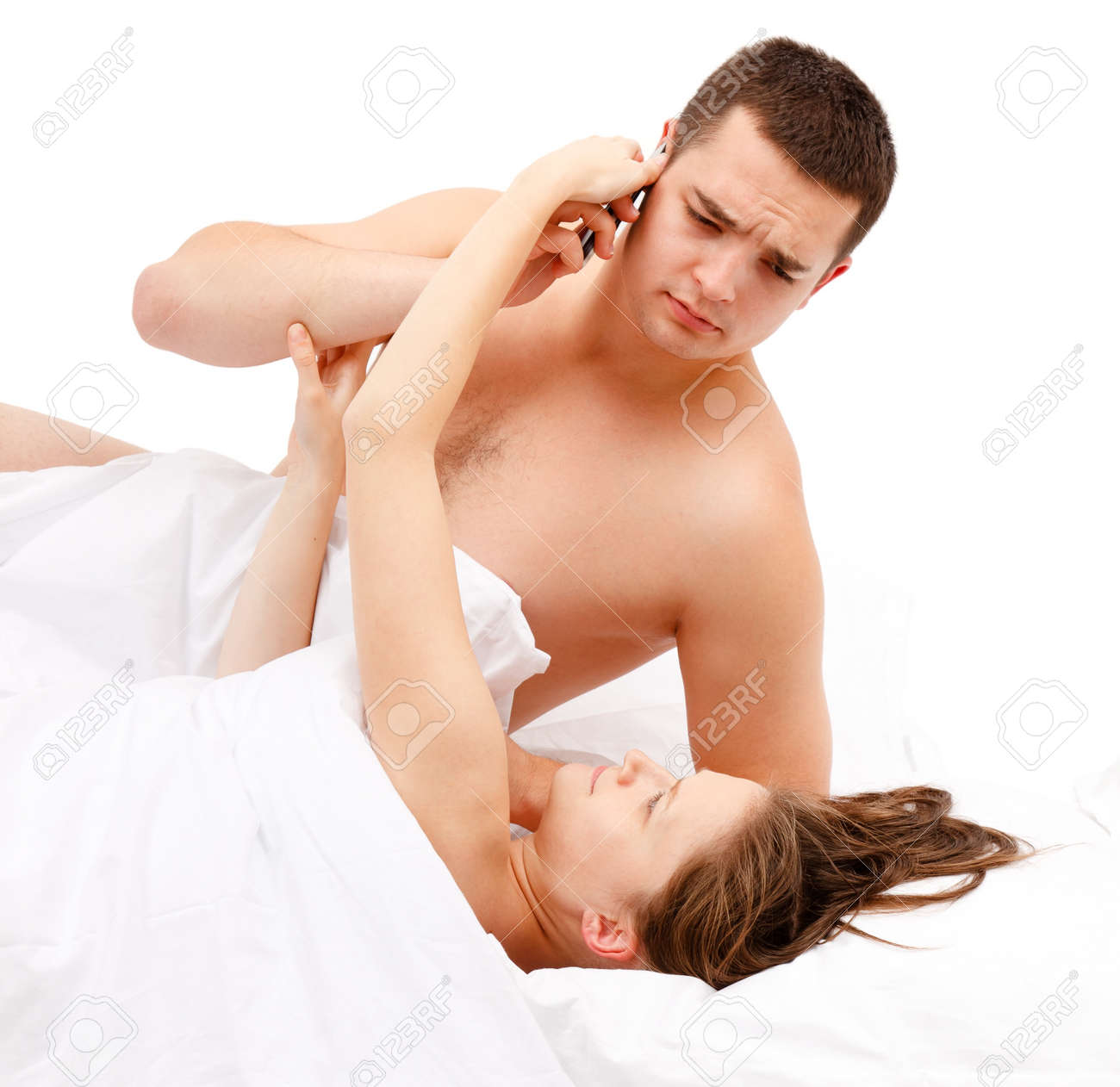 Naked couple in bed, woman trying to take phone from man while he's still speaking Stock Photo - 10658816
