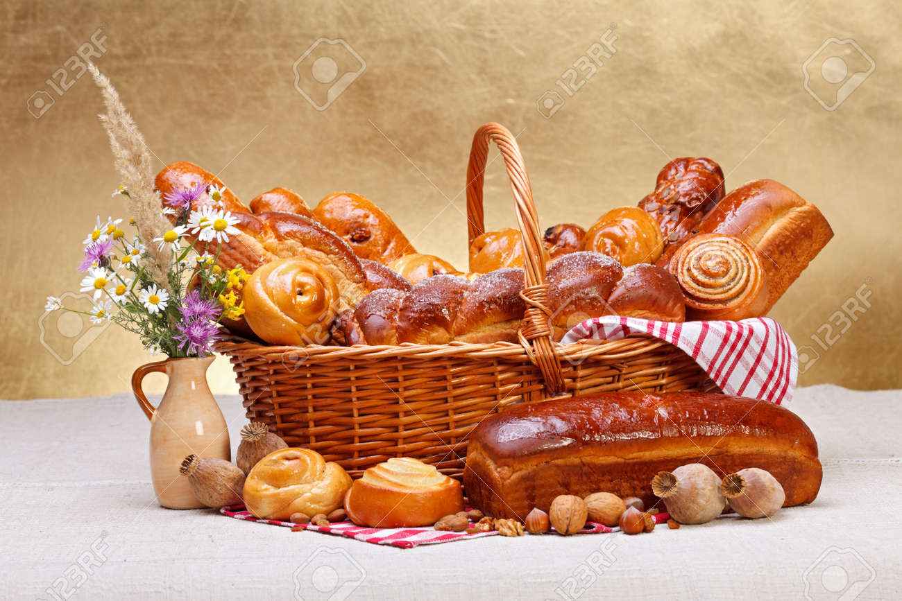 Sweet bakery products in basket, wild flower decoration, rustic background Stock Photo - 17688270