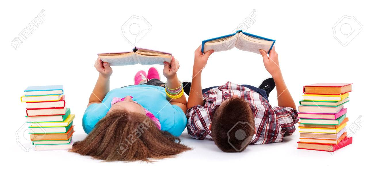 Teens with books next to them laying on the floor and reading - 22519437