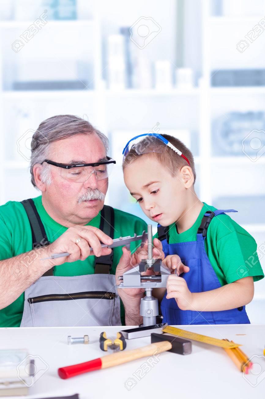 Grandfather teaching grandchild measuring with vernier caliper - 23880330