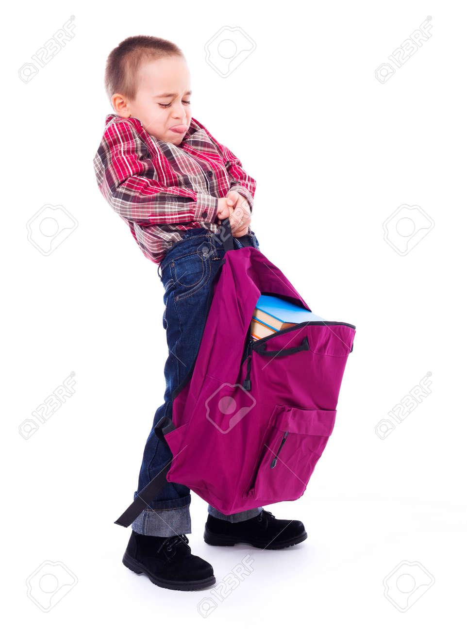 Little boy lifting big, heavy schoolbag full of books - 23955979
