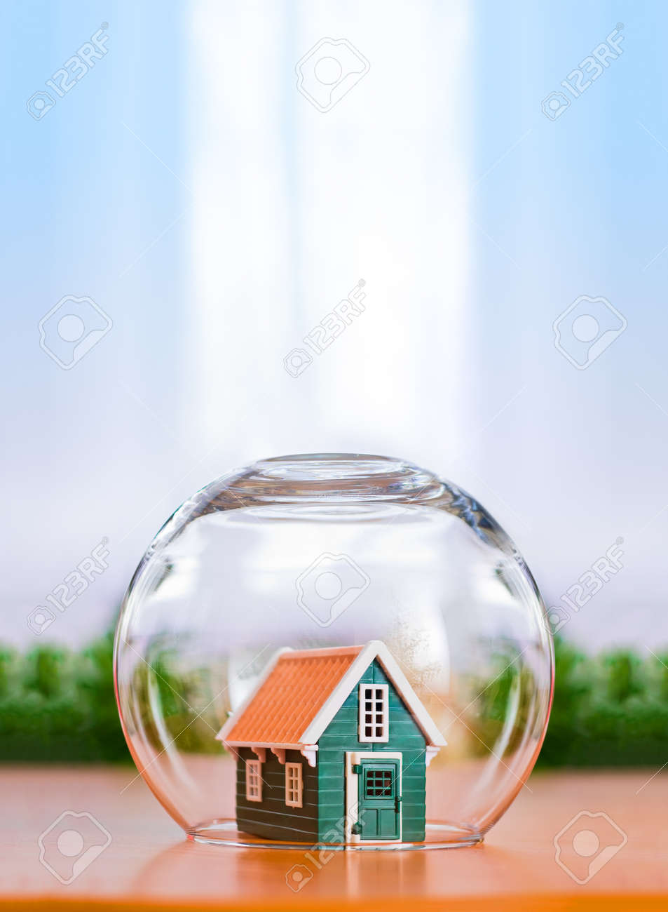 Insured house concept. Toy house protected in glass sphere with copy space above - 35244009