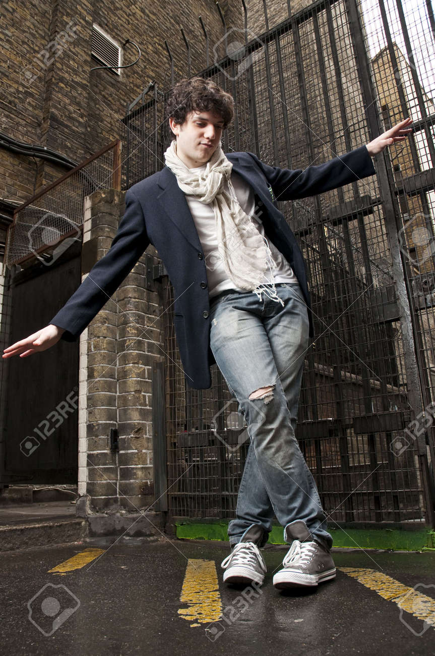 Low angle portrait of young man dancing with gate in the background. Stock Photo - 6687497