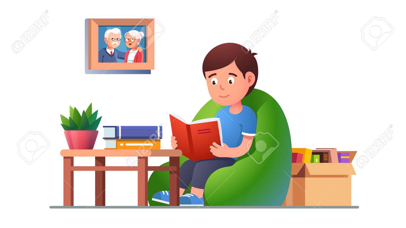 Kid reading book sitting on bean bag chair - 153086096