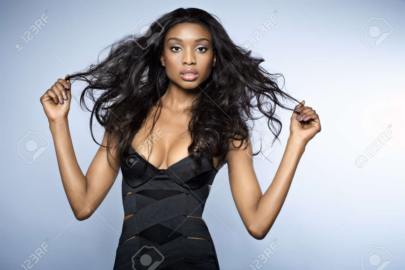 Black dress hairstyle - African Young Woman With Long Hair Wearing Small Bandage Black Dress On Blue Background It