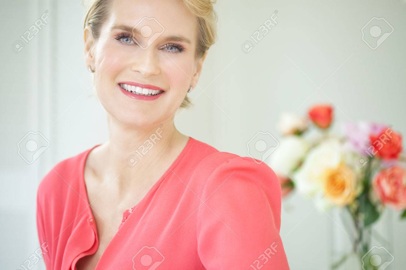 2fd586060379b Beautiful smiling elegant woman indoors wearing pink blouse and short blond  hair. Stock Photo -
