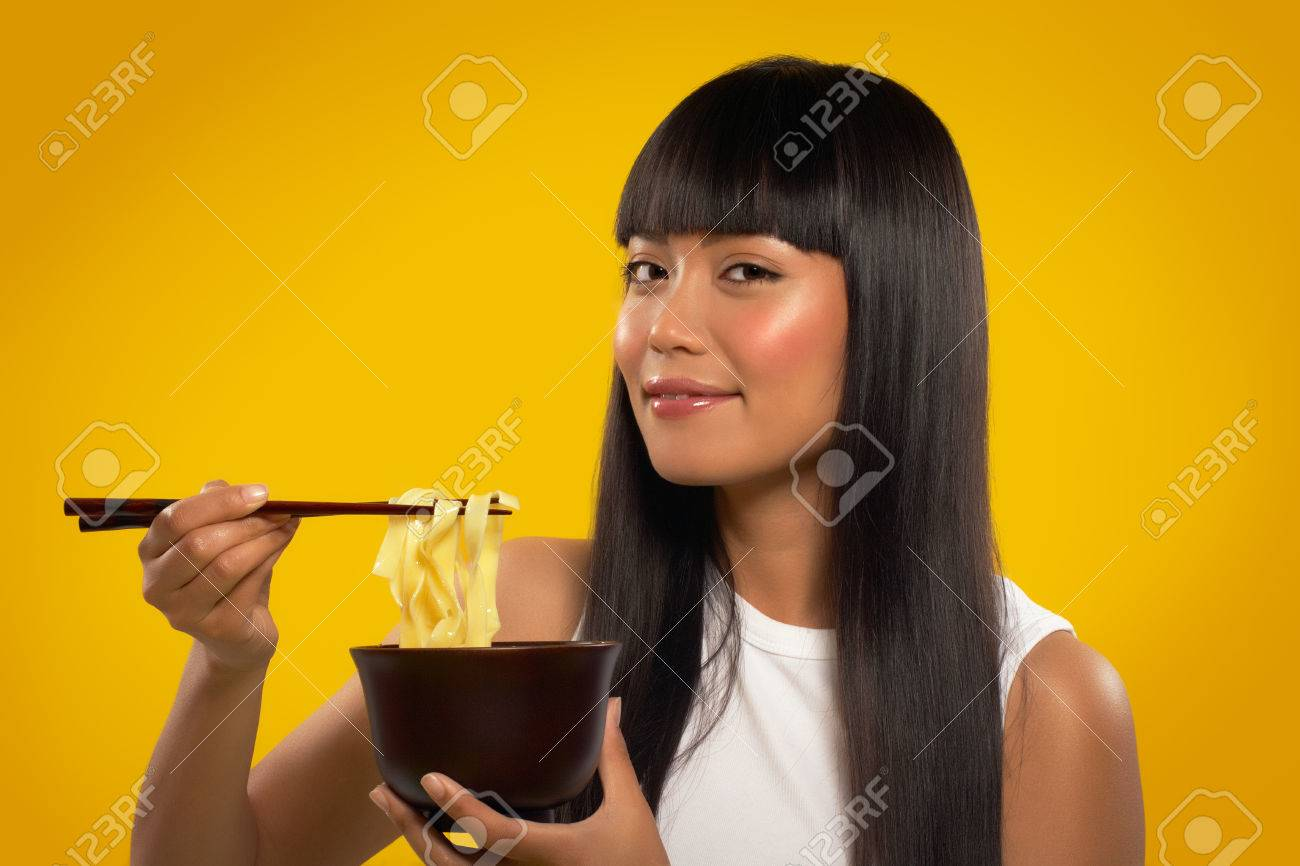 Cheerful Asian girl with noodles and chopsticks. - 38409440