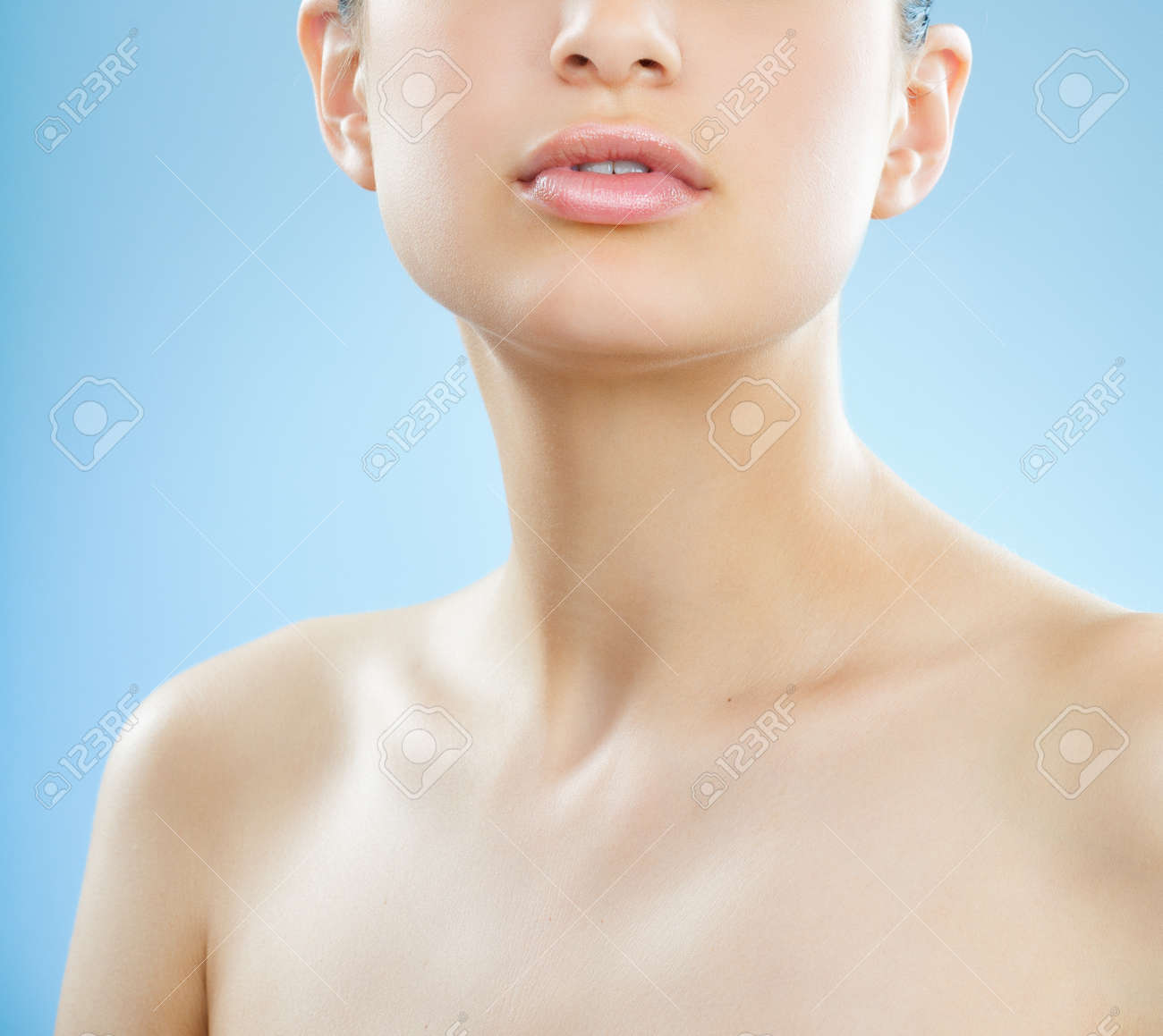 Beautiful young European woman with fresh smooth glowing skin and full lipst over blue background. - 38854282