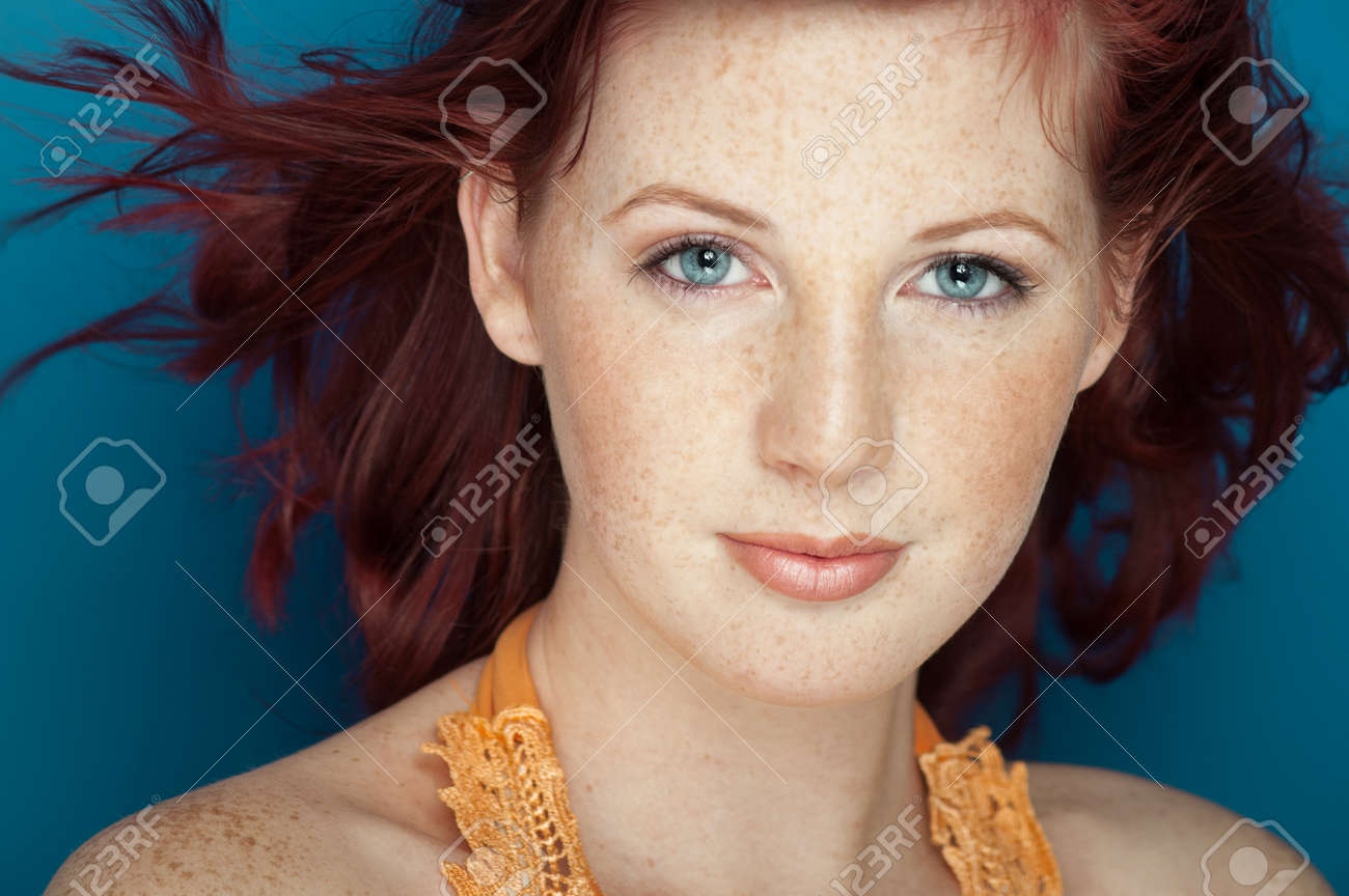 Beautiful fresh girl with auburn hair, blue eyes and freckles posing over blue background. - 38858942