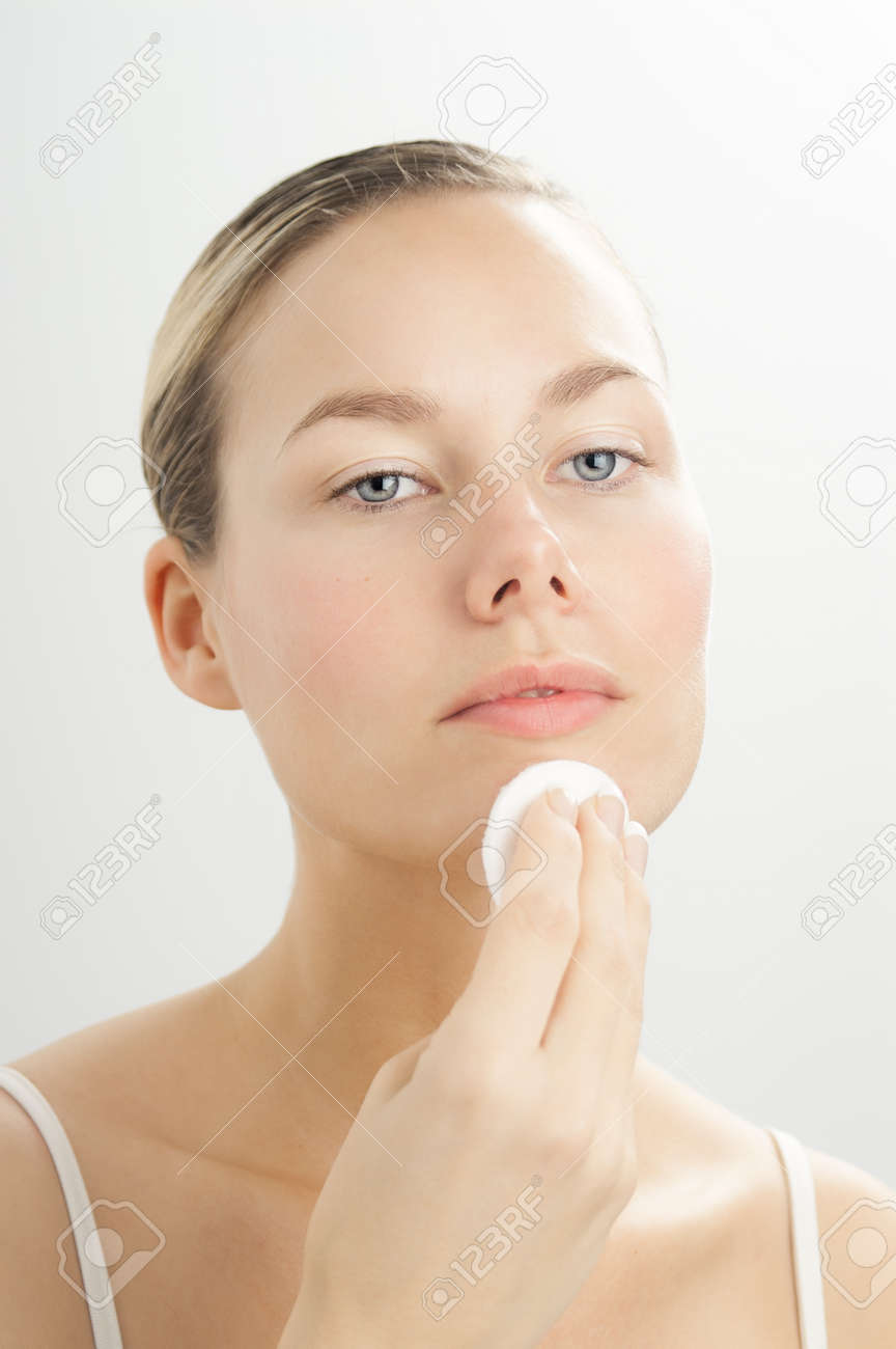 Young beautiful woman cleansing face with toner on cotton disk