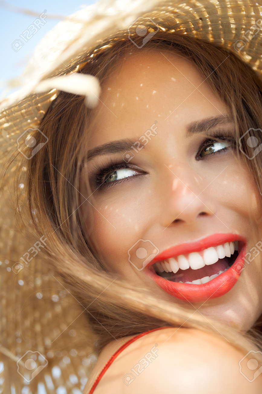 Young woman in straw hat smiling in summer outdoors. - 39840315