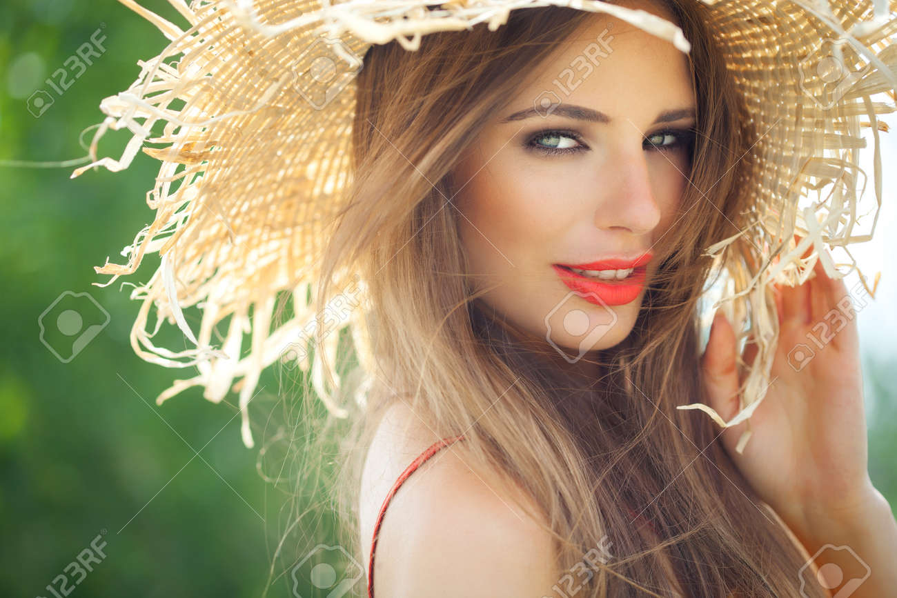 Young woman in straw hat smiling in summer outdoors. - 39840316