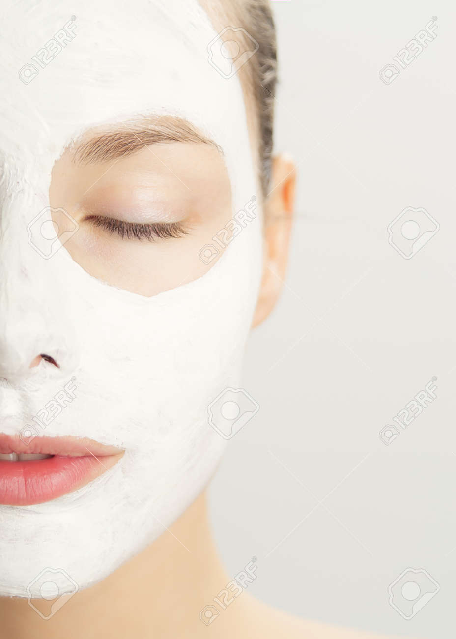 Closeup of beautiful young woman with white clay cosmetic mask. Skincare using masks. White clay clarifying facial mask. - 40763096