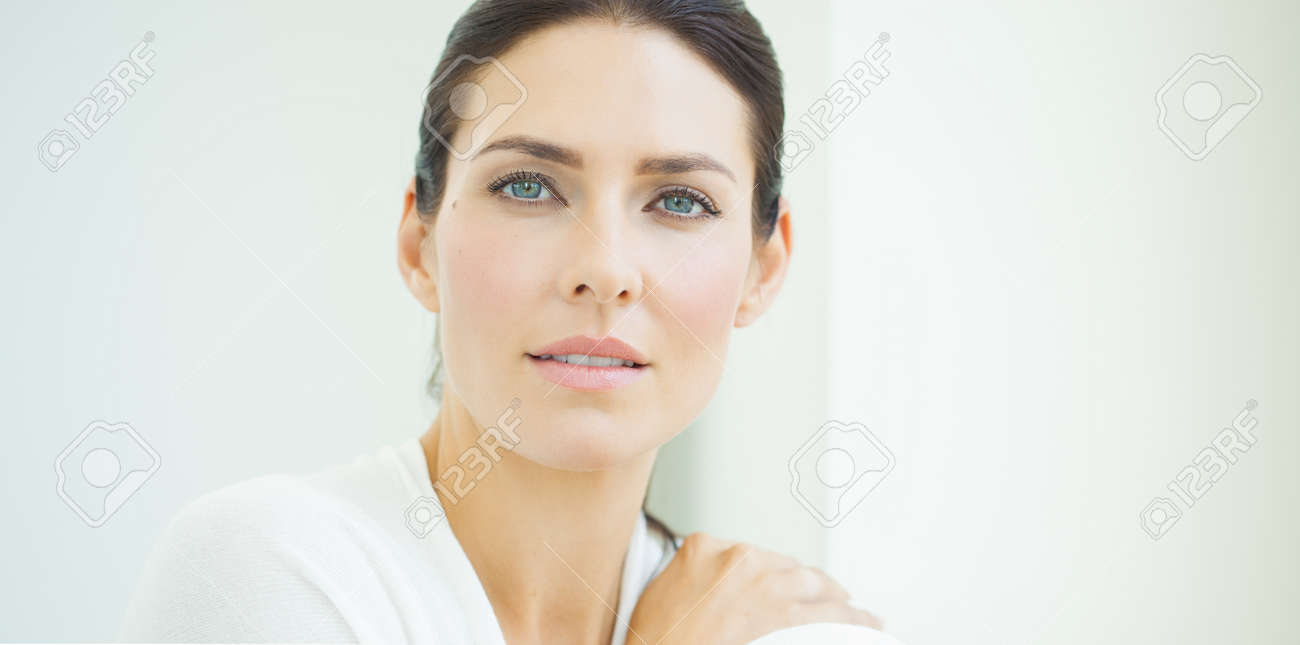 Beautiful natural European woman sitting in daylight at window with serene expresssion. Blue eyes and dark hair. - 45643610